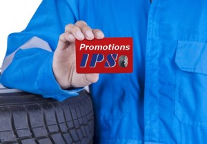 Closeup of male mechanic with blue uniform standing near tires and showing a gift card